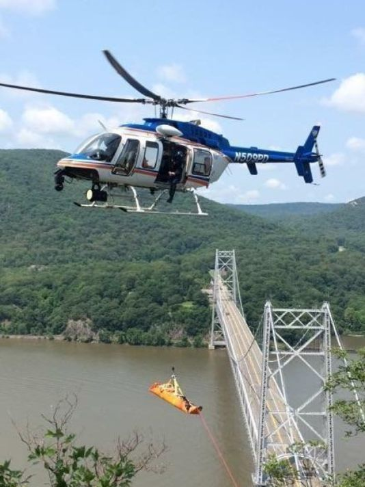 A police helicopter hoists an injured hiker near the Bear Mountain Bridge on Sunday. (Westchester County Police Photo)