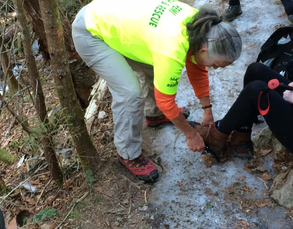 A member of the Pemigewasset Valley Search and Rescue Team places a traction device on the boot of a struggling hiker on Sunday. (Pemigewasset Valley Search and Rescue Team/Facebook Photo)